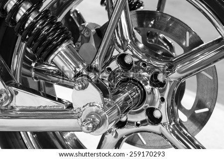 Front wheel of high power big custom motorcycle with chrome parts - monochrome, blurred selective focus