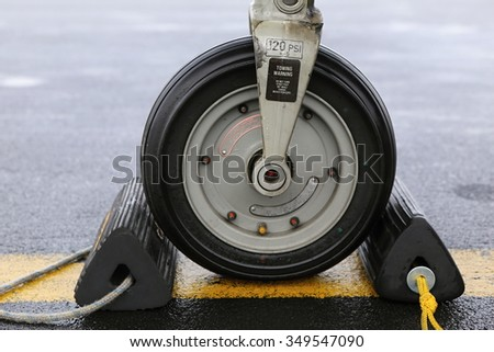 Front wheel of the aircraft with black parking blocks - stock photo
