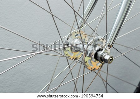 Front wheel of the bike with plaster wall background - stock photo