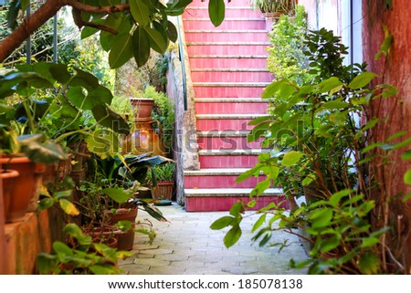 Front yard of the building in Anacapri island, Italy. Intimate garden with pink staircase and some old jars.  - stock photo