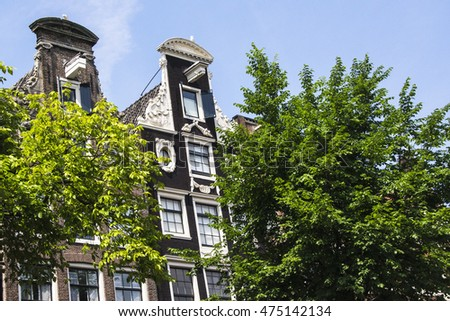 frontage of houses on a canal in Amsterdam against a blue sky