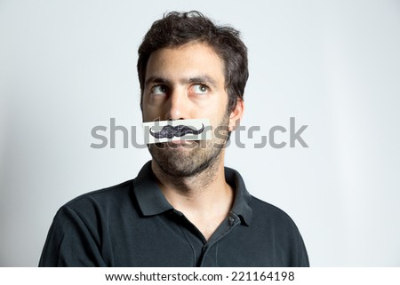 frontal portrait of young man with fake moustaches - stock photo
