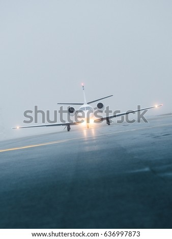 Frontal view of a silver-gray airplane on taxiway during a foggy day