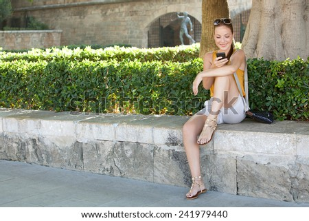 Frontal view of a young and beautiful tourist woman sitting in a green park holding and using her smartphone to network while visiting a destination city on holiday. Travel and lifestyle technology.