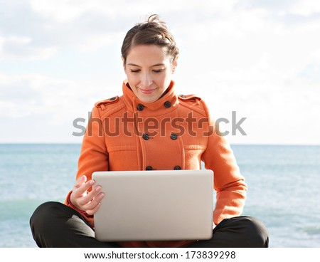 Frontal view of a young professional woman sitting down with her legs crossed by the ocean with a sunny blue sky, using a laptop computer and working on it during a break. Outdoors technology. - stock photo