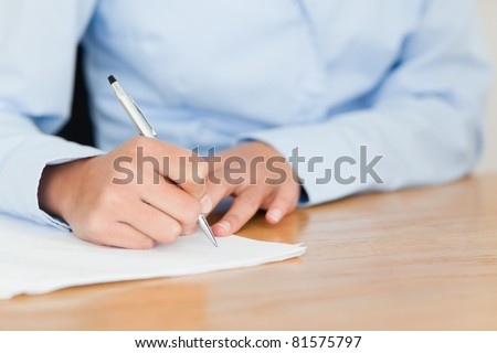 Frontal view of a young woman writing on a sheet of paper while sitting at the office - stock photo