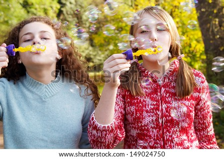 Frontal view of two teenager friends playing games together and blowing soap bubbles up in the air while in a natural park during a fall autumn sunny day, outdoors. - stock photo