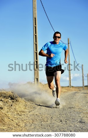 frontal view of young sport man with sun glasses running on countryside track with power line poles training in summer in cross country runner concept and healthy fitness lifestyle - stock photo
