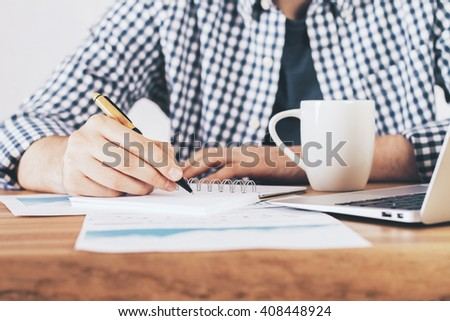 Frontview of male hand writing in spiral notepad on desk with coffee mug, laptop and business report - stock photo