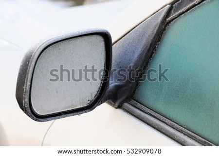 frost and ice on vehicle side view mirror in winter morning