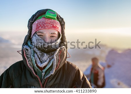 Frost Portrait of a hiker Climber. Wrapped in frosty hat and scarf - stock photo