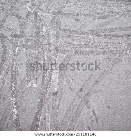 Frosted asphalt covered with the tire tracks as a background composition - stock photo
