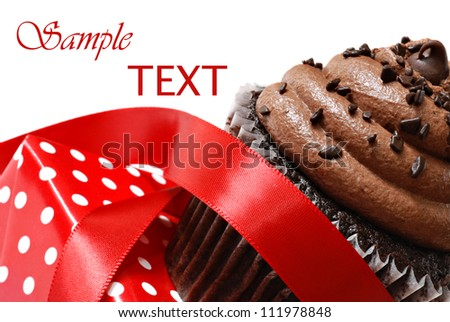Frosted chocolate fudge cupcake with red satin ribbon and polka dot gift box on white background with copy space.  Macro with shallow dof. - stock photo