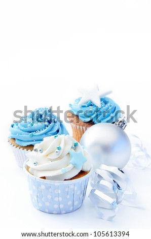 Frosted cupcakes in cool tones with silver christmas bauble and white ribbons - stock photo