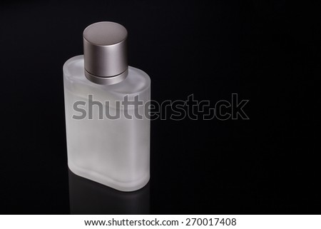 Frosted perfume bottle on a black background. With room for copyspace - stock photo