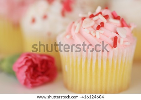 Frosted pink vanilla cupcakes with a rose, sprinkles and a blurred background. - stock photo
