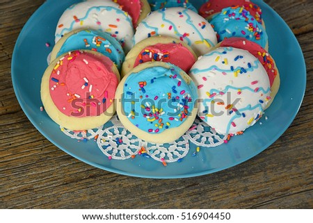 frosted sugar cookies with sprinkles on turquoise plate and rustic wood