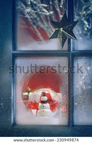 Frosted window with Christmas decoration inside at night - stock photo
