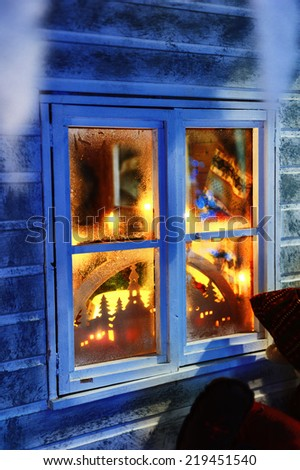 Frosted window with Christmas decorations and festive lights  - stock photo