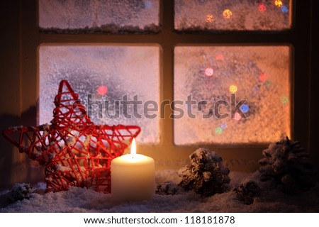 Frosted window with festive candles and holiday decorations - stock photo