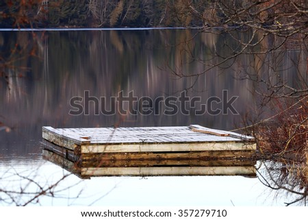 frosty dock icy water fall trees reflecting in calm water of lake in autumn - stock photo