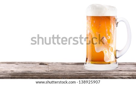 Frosty fresh beer with foam isolated on a vintage wooden table