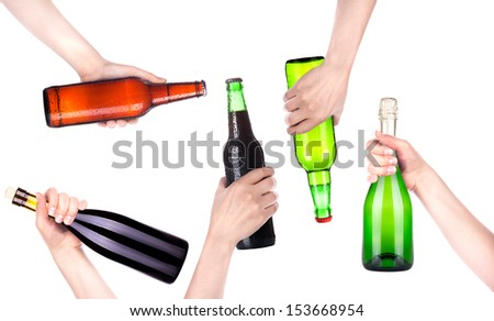 Frosty fresh bottle of beer, champagne and wine in a hand making toast - stock photo