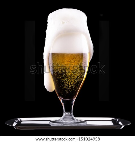 Frosty glass of light beer  isolated on a black background
