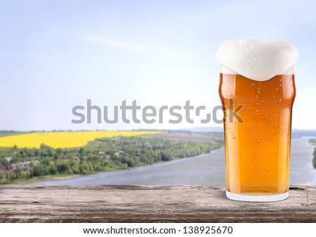 Frosty glass of light beer on a wooden table with summer scene background