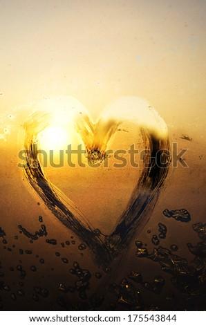 Frosty heart on window at sunset - stock photo