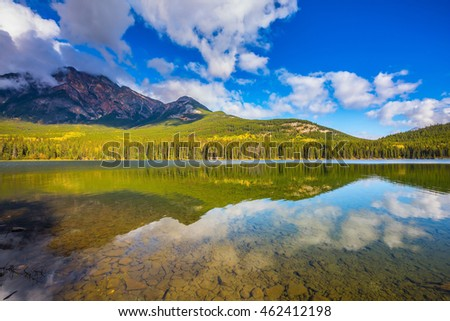 Frosty morning in the Rocky Mountains, Canada. Clear water Pyramid Lake reflects the clouds and pine forests on the shore