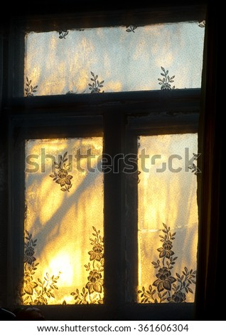 Frosty morning in village in rising sun beams - stock photo