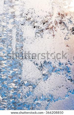 frosty pattern on edge of frozen winter window glass - stock photo