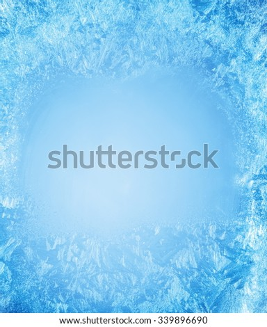 Frosty patterns on the edge of a frozen window. - stock photo