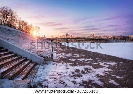 Frosty promenade overlooking the bridge in the evening sunset