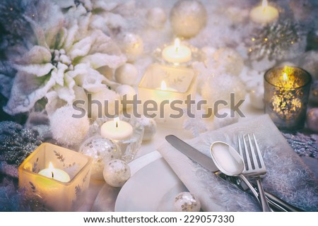 Frosty White Christmas Scene Table Place Setting with Poinsettia, Candles, Snowballs and Snowflakes with room or space for copy, text, your words. Horizontal, dramatic and moody dark vintage tones - stock photo