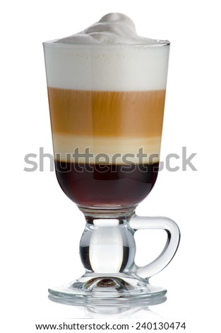 Frothy, layered cappuccino in a clear glass mug with cinnamon sprinkled isolated - stock photo