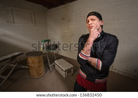 Frowing tough European man with radio in background - stock photo