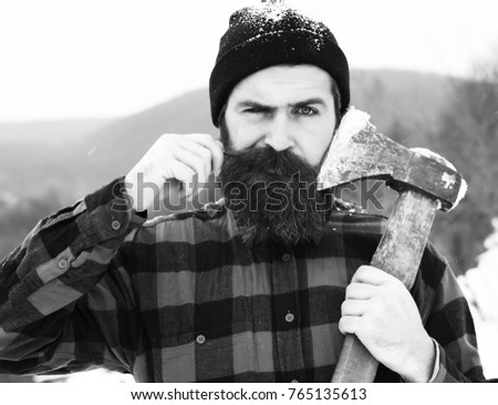 Frown man or brutal lumberjack, bearded hipster, with beard and moustache in red checkered shirt shaves with axe blade in snowy forest on winter day outdoors on natural background
