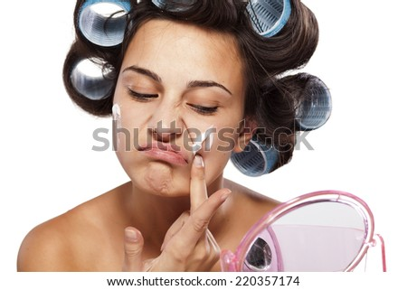 frowning and unsatisfied woman with curlers applied face cream - stock photo