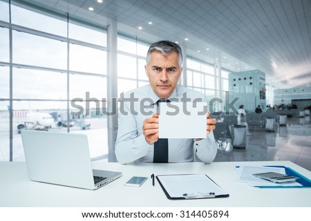 Frowning bank clerk at desk holding a sign and rejecting a loan application - stock photo
