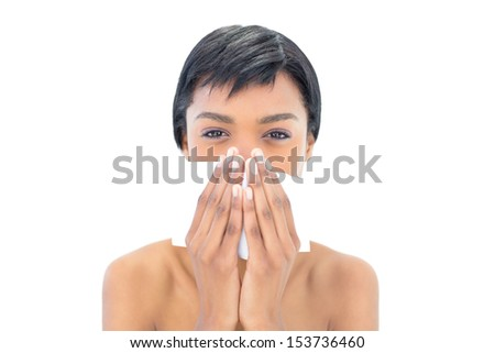 Frowning black haired woman using a handkerchief on white background