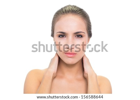 Frowning brunette woman having a sore neck on white background