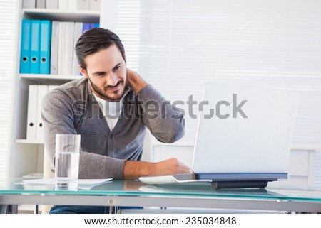 Frowning handsome businessman having neck pain in the office - stock photo