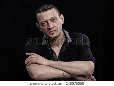 Frowning man portrait on black - stock photo