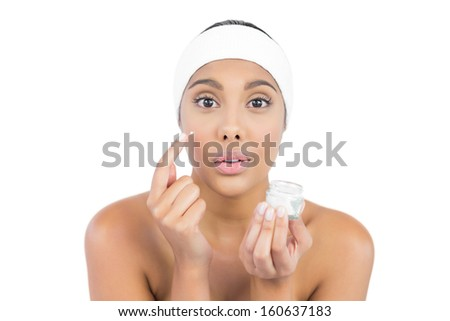 Frowning nude brunette using moisturizer looking at camera on white background