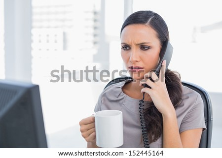 Frowning secretary answering phone in her office