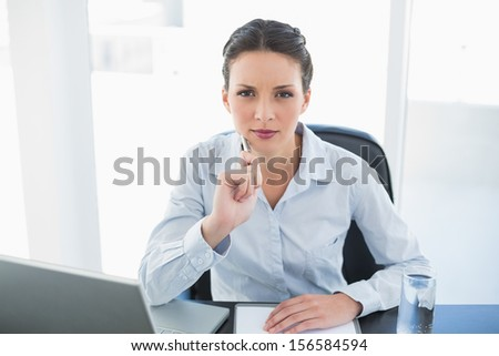 Frowning stylish brunette businesswoman holding a pen and looking at camera in bright office