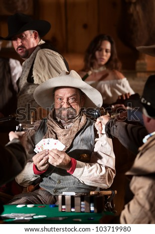 Frowning winner with guns pointed at him in old west saloon - stock photo