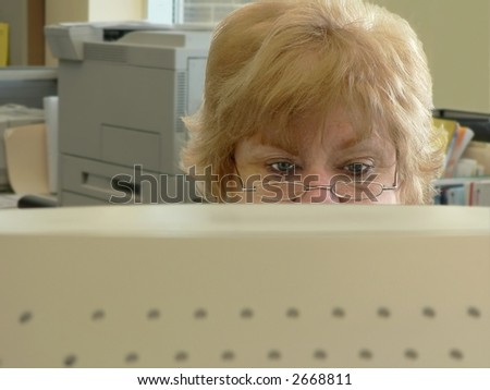 Frowning woman at computer - stock photo